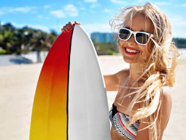 Close up of a young woman holding a surfboard