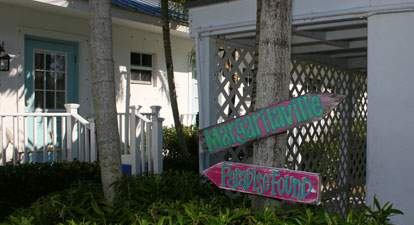 Entryway to Bungalows, palm and directional signs reading Margaritaville and Paradise Found