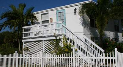 Two-story white building with exterior stairs going to upstairs bungalow, white picket fence